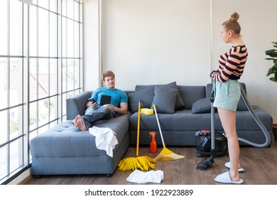 Couple playing doing chores. Cheerful couple having fun while doing housework together. Happy young Caucasian couple playing and talking to each other while doing their housework cleaning their home.