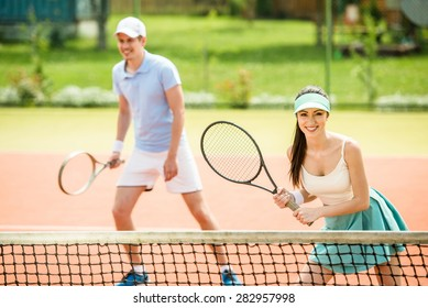 Couple playing doubles at the tennis court.
