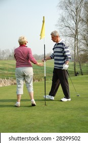couple playing golf on the green