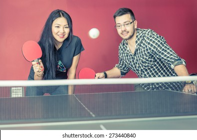 couple playing ping pong in a bar. concept about friends, couple, activity, sport, leisure and people