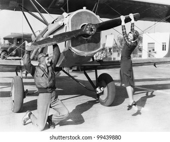 Couple playing with propeller on plane