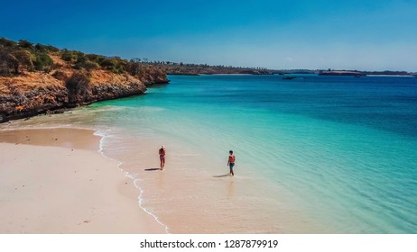 A couple playing in the sea on the Pink Beach in Lombok. Hidden gem, not spoiled by tourists. Solitude and calm feelings, waves gently spreading on the beach. turquoise color of the water.