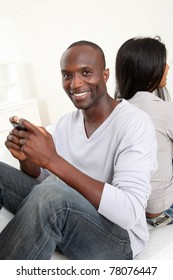 Couple playing with smartphone at home