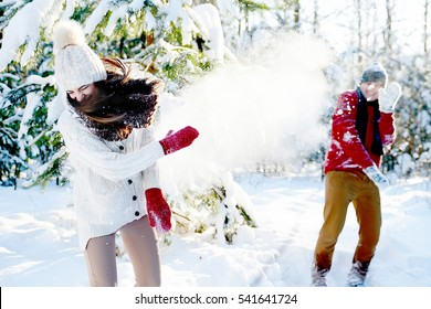 couple playing snowballs in a snowy forest