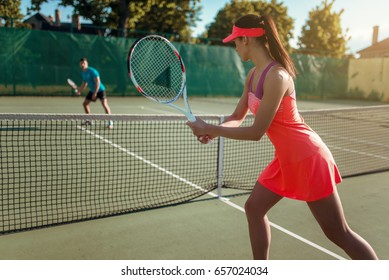 Couple playing tennis on outdoor court