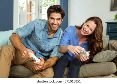 Couple playing video game while sitting on sofa in living room