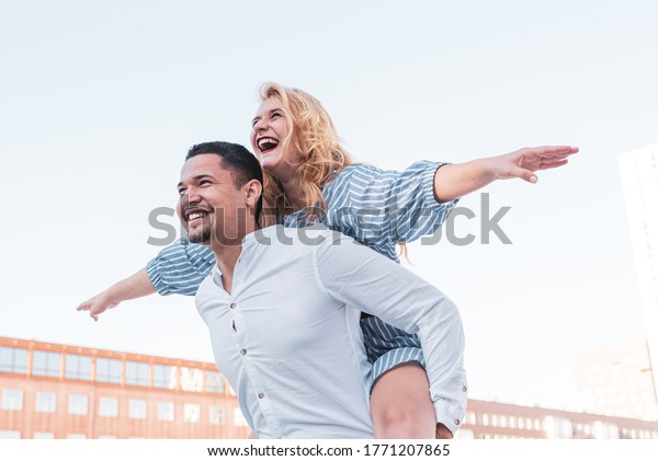 a couple plays happily, she on his back opens her arms and pretends to fly, he carries her with joy,  happy and optimistic smiles of a multi-ethnic couple, concept of romance, freedo and love