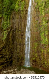 A couple plays in Waimoku Falls - a waterfall in Haleakala National Park, Maui, Hawaii