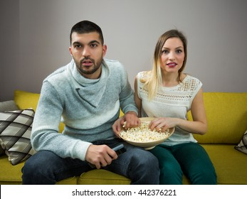 Couple with popcorn watching movie at home
