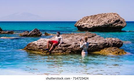 Couple at Porto Zorro beach taking a healing mud bath with clay. Zakynthos island. Greece