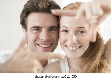 couple portrait forming a frame with their hands