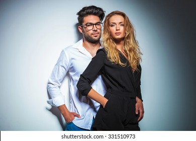 couple pose in studio close to each other with hands in pockets while looking at the camera