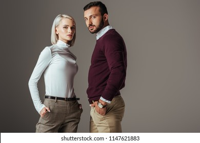 couple posing in fashionable autumn outfit, isolated on grey