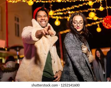 Couple posing for funny photo at Christmas market, Zagreb, Croatia.