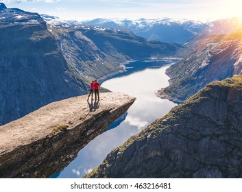 Couple posing on Trolltunga. Happy woman and man enjoy beautiful lake and good weather in Norway.