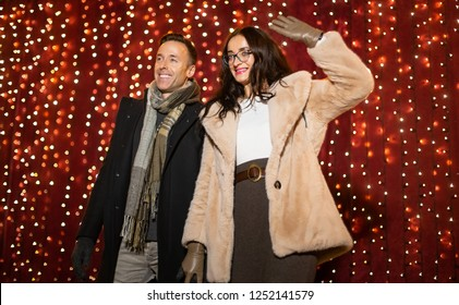 Couple posing for photo in front of light wall at Christmas market.
