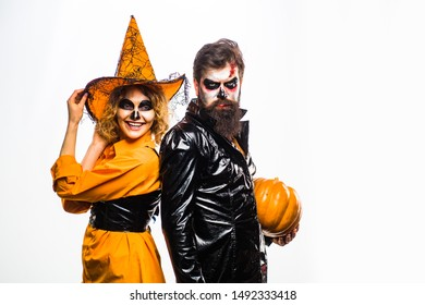Couple posing with Pumpkin. Beautiful surprised woman in witch hat and costume - showing products. Halloween design for copy space