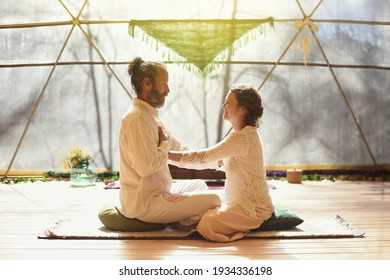 Couple practicing tantra and meditation techniques, hand on heart.