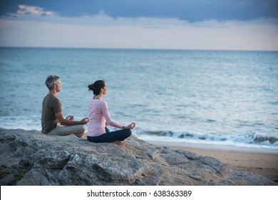 Couple practicing yoga at sunrise on the beach facing the sea