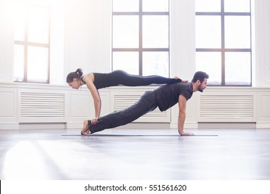 Couple practicing yoga together doing plank and chaturanga