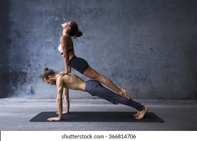 Couple practicing yoga together, upward facing dog on top of plank pose