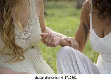 couple of premarital married women are engaged, faceless, women sit in wedding dresses, holding hands in nature. Touches, love, delicate arms, wearing white wedding dresses, lesbians, partners