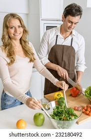 Couple preparing a healthy meal with fresh vegetables and fruit