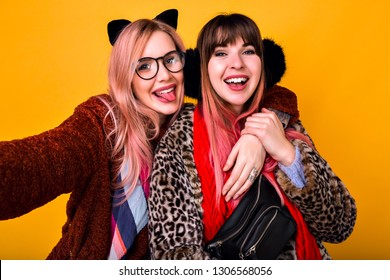 Couple of pretty funny hipster best friends sister girls making selfie at yellow background, showing tongue and smiling, wearing trendy spring printed fur coats, scarfs, bum bag and clear glasses.