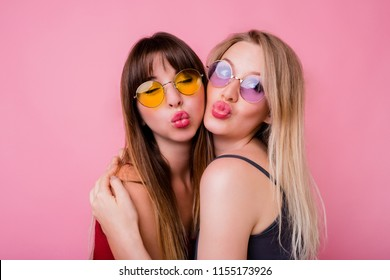 Couple of pretty girls, best friends posing on pink background. Two women in colorful sunglasses send  kiss.