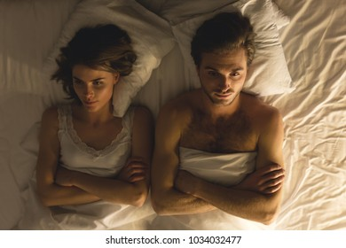 Couple problem. Couple lies in the bed at evening time after the quarrel.