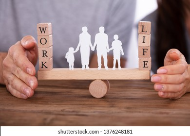 Couple Protecting Work And Life Balance With Family Figures Standing Between Them On Seesaw