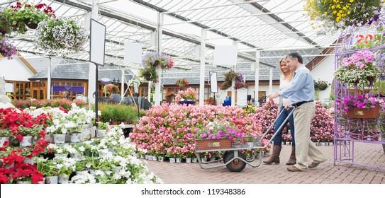 Couple pushing trolley in garden center