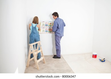 Couple putting up wall papper in baby room