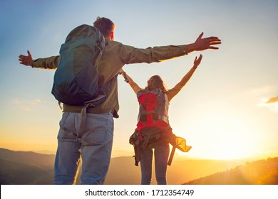 Couple with raised arms holding hands and looking at sunset