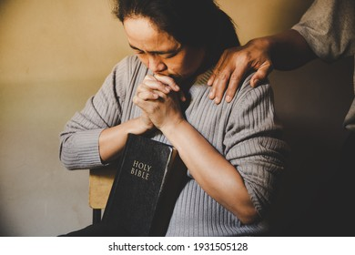 Couple reading bible and pray together at home. Two people are praying together. close hands