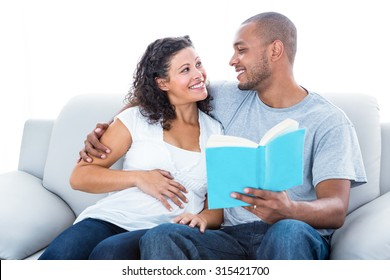 Couple reading book relaxing at home