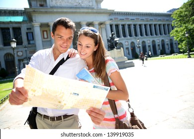 Couple reading city map in front of Prado museum, Madrid