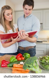 Couple reading cookbook together in kitchen