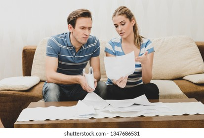 Couple reading an important notification in a letter while sitting on sofa.