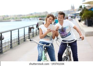 Couple reading map on bike tour