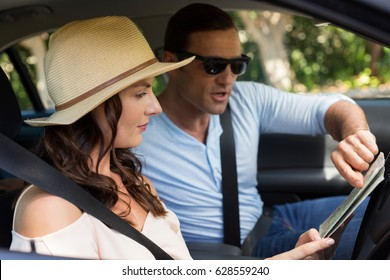 Couple reading map while traveling in car