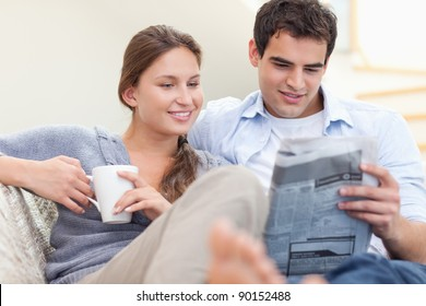 Couple reading the news while lying on a sofa looking away from the camera