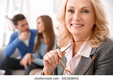 Couple at real estate sales office with agent smiling joyful close-up
