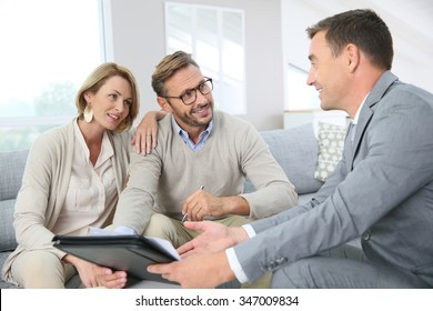 Couple with realtor signing mortgage contract