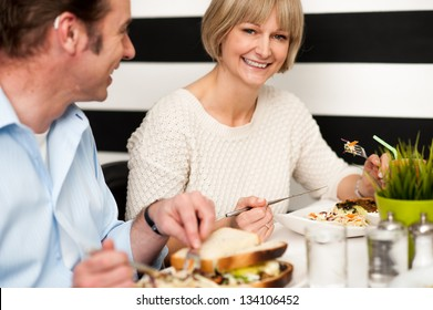 Couple recalling old memories while dining in a food court.