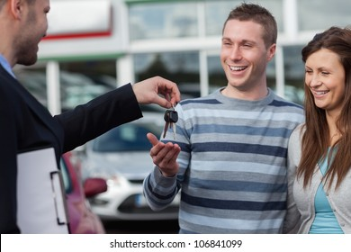 Couple receiving car keys by a dealer in a dealership