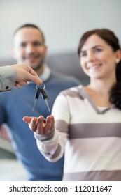 Couple receiving keys in a car shop