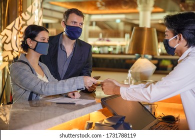 Photo of Couple and receptionist at counter in hotel wearing medical masks as precaution against virus. Young couple on a business trip doing check-in at the hotel