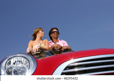 Couple in red convertible car