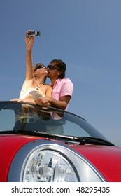 Couple in red convertible car taking picture